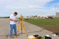 Student sets up surveying equipment